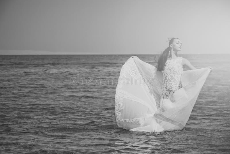 Wittebroodswekenreis Bruid op zonnige de zomerdag op blauw water stock afbeelding
