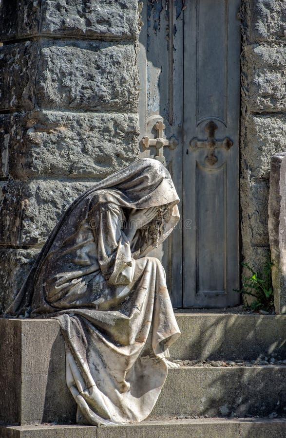 Witwe während schreiende Marmorstatue außerhalb eines Grabs stockbild