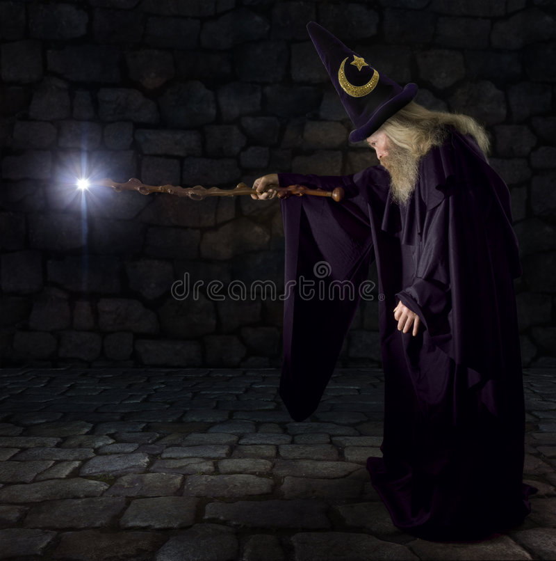 The Wizard. Wizard in a purple robe and wizard hat casting a spell with his wand stock images