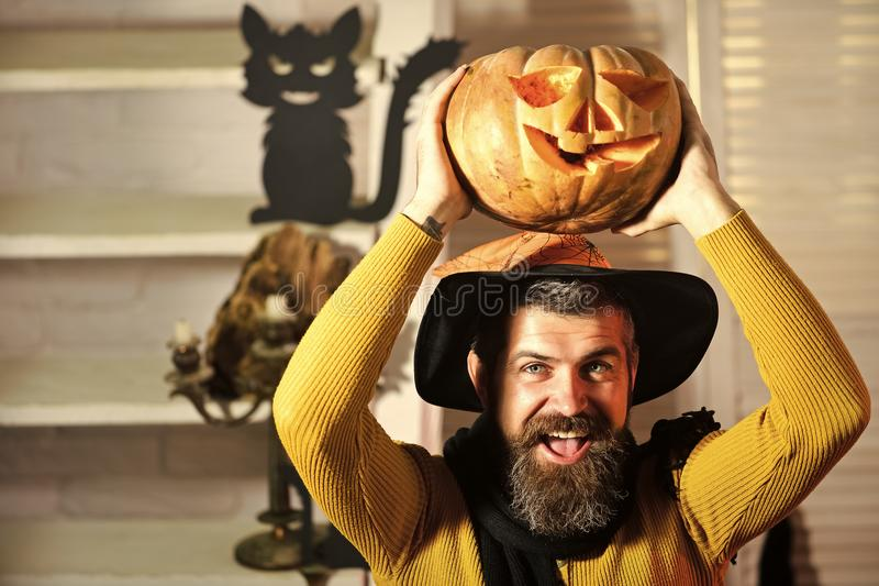 Wizard in black witch hat on spooky room background. Defocused. Man with beard and happy face holds jack o lantern. Magician and carved pumpkin. Halloween royalty free stock images