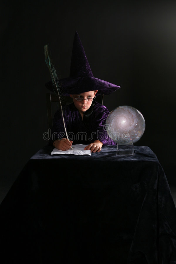 Wizard boy writing with a feather. Wizard boy looking into crystal ball and writing with a feather pen stock images