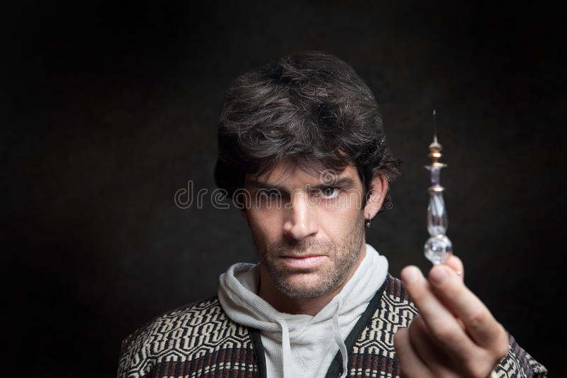 Wizard Holds Potion Bottle. Serious young Caucasian wizard holds potion bottle stock photos