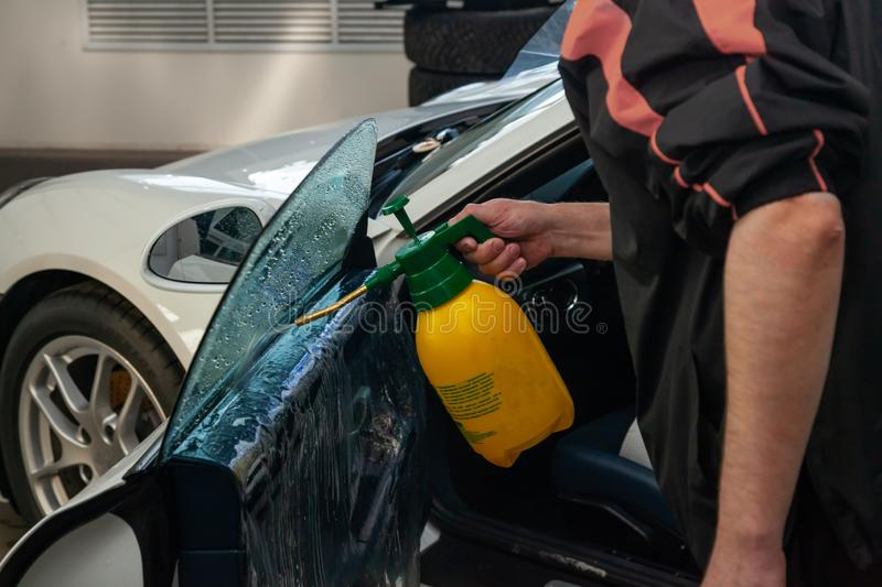 The wizard for installing additional equipment sticks a tint film on the side front glass of the car and sprays water to get wet stock images