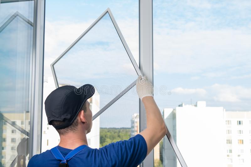 The wizard for installing plastic windows installs a mosquito net in the window royalty free stock photography