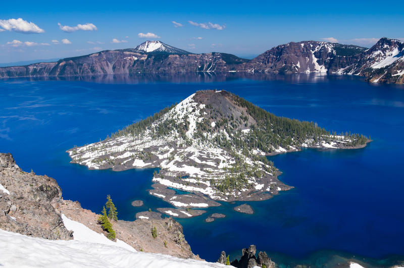 Wizard Island in Crater Lake. View of Wizard Island in Crater Lake with snow cover royalty free stock images