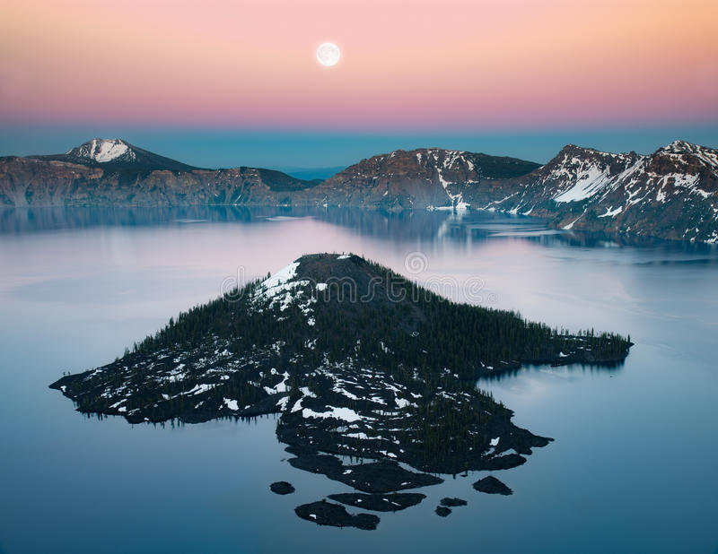 Wizard island and full moon. This is a photograph of Wizard Island and full moon at sunset hour stock photography