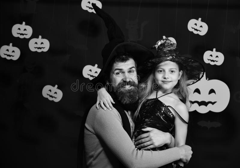 Wizard and little witch in black hats. Father and daughter. Wizard and little witch in black hats hug. Father and daughter in Halloween costumes. Halloween party royalty free stock photo