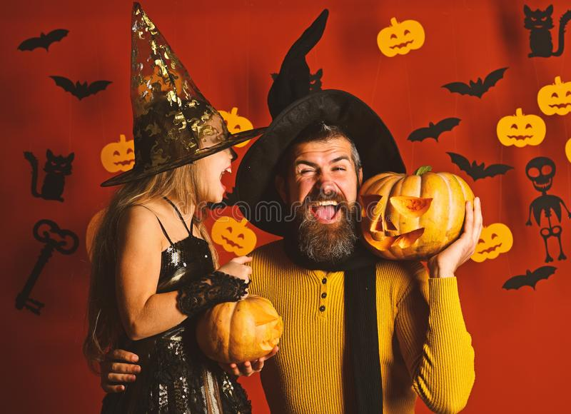 Wizard and little witch in black hats hold pumpkins. Father and daughter in costumes. Halloween party and celebration concept. Girl and bearded men with royalty free stock images