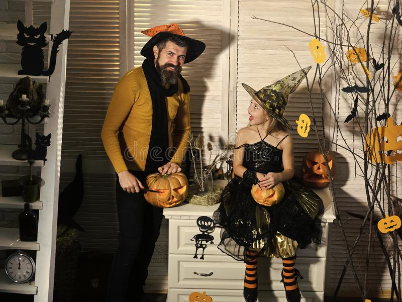 Wizard and little witch in hats carve pumpkins. Halloween party concept. Girl and bearded men with interested faces on spooky carnival room background. Father stock image