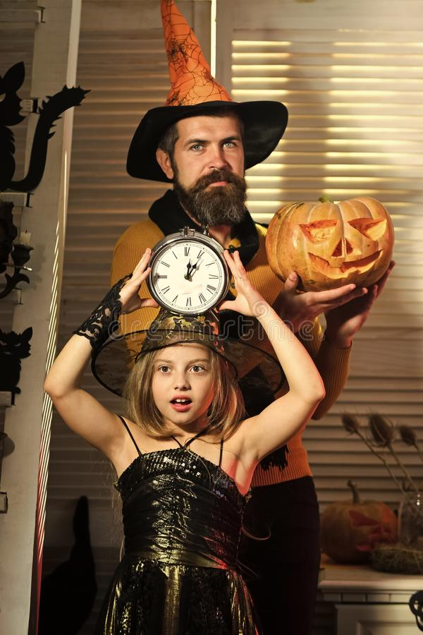 Wizard and little witch in hats hold clock and pumpkin. Father and daughter with Halloween decor. Halloween party concept. Girl and bearded men with concerned royalty free stock image