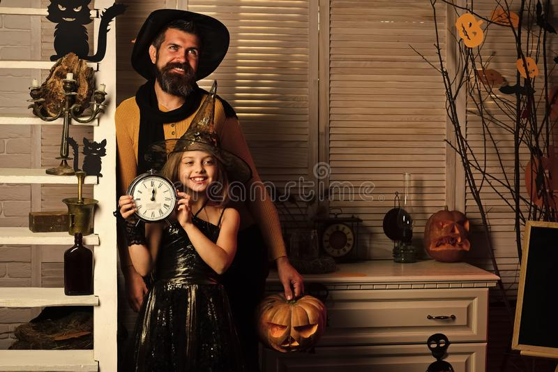 Wizard and little witch in hats hold clock and pumpkin. Halloween party concept. Father and daughter with Halloween decor. Girl and bearded men with smiling royalty free stock photography