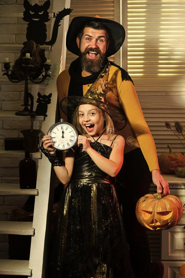 Wizard and little witch in hats hold clock and pumpkin. Wizard and little witch in hats hold old clock and pumpkin. Halloween party concept. Dad and daughter royalty free stock photo