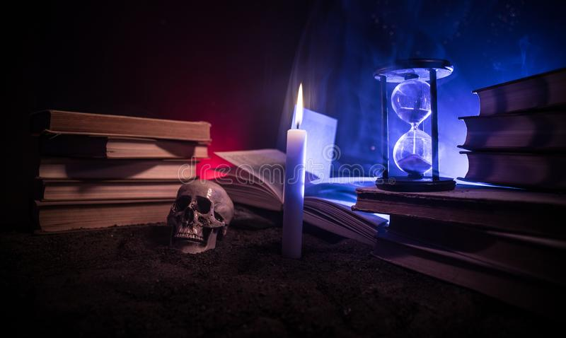 Wizard's Desk. A desk lit by candle light. A human skull, old books on sand surface. Halloween still-life background with a diffe. Rent elements on dark toned stock photo