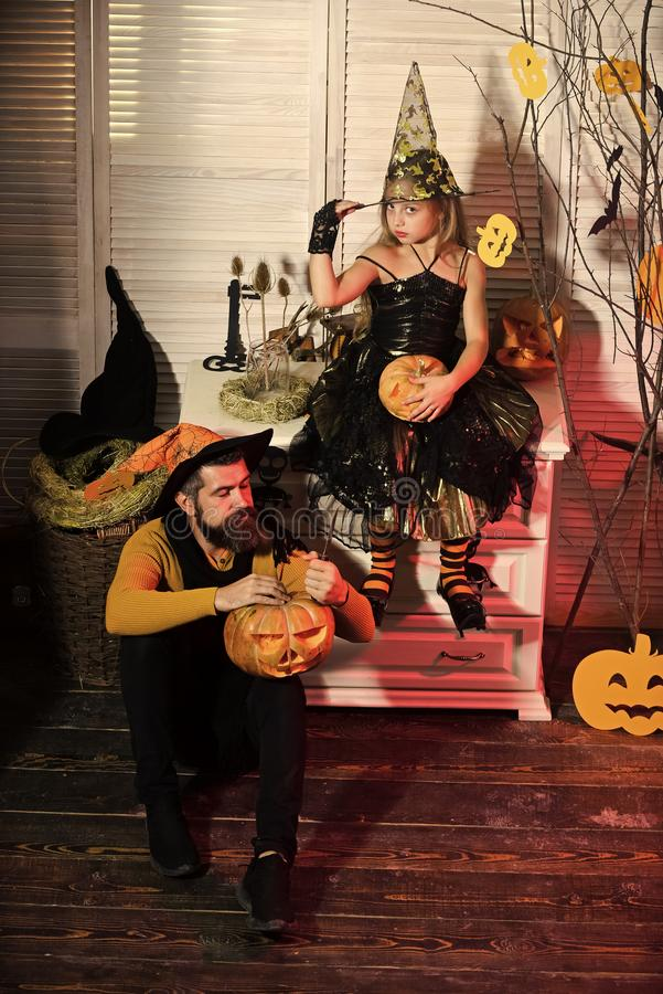Wizard and witch in hats carve pumpkins. Father and daughter. Wizard and little witch in hats carve pumpkins. Father and daughter with Halloween decor. Girl and royalty free stock images