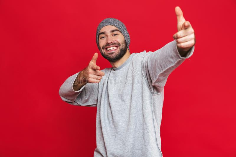 Wizerunek śmia się i wskazuje optymistycznie mężczyzna dotyka na kamerze odizolowywającej nad czerwonym tłem obraz royalty free