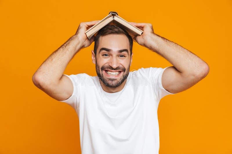 Wizerunek śmieszny mężczyzna 30s w białej koszulce trzyma książkę na jego głowie, odosobniony nadmierny żółty tło obrazy royalty free