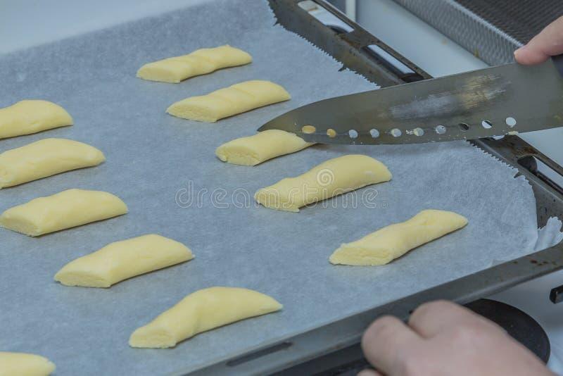 Wizerunek świezi surowi ciastka które są na wypiekowej tacy i z nożem robią twoo szczelinom jako dekoracja zdjęcia royalty free