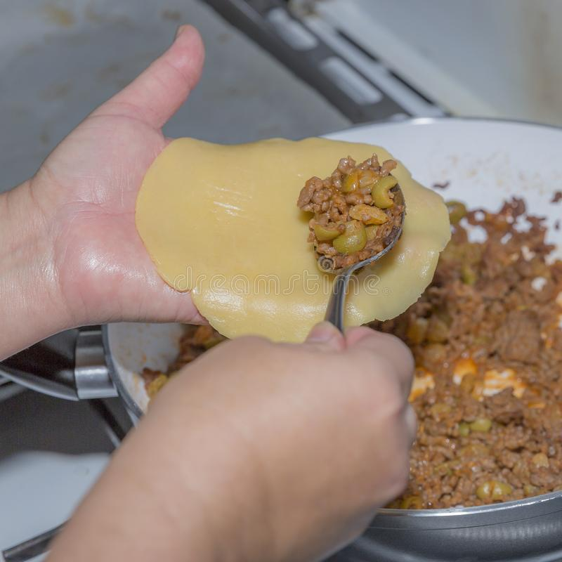 Wizerunek żeńskie ręki spooning zmieloną wołowinę przygotowywał z oliwkami na świeżym surowym cieście empanada obrazy stock