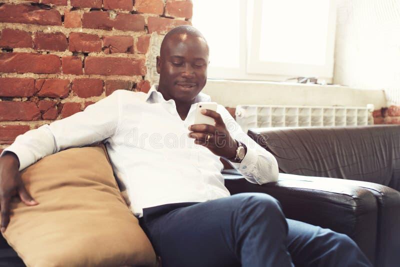 Wizerunek amerykanina afrykańskiego pochodzenia fachowy biznesmen w biznesowym formalnym ubiorze na jego mobilnym komórki smartph zdjęcia stock