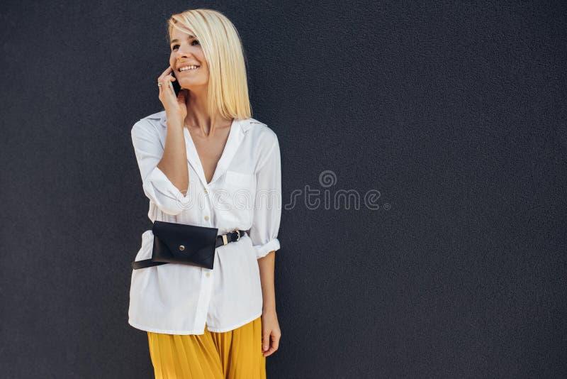 Wizerunek atrakcyjna blondynki biznesowej kobiety pozycja w szarej budynek ścianie podczas gdy opowiadający na jej telefonie komó obraz stock