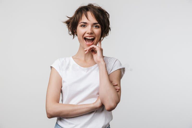 Wizerunek atrakcyjna kobieta ono uśmiecha się przy kamerą w podstawowej koszulce podczas gdy stojący z rękami krzyżować obrazy stock