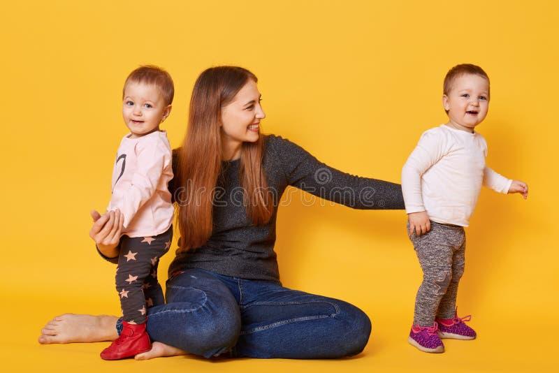 Wizerunek atrakcyjnego brązu z włosami matka chce fotografującym z jej słodkimi dziećmi, siedzi na podłodze w studiu Matka i dzie zdjęcie stock