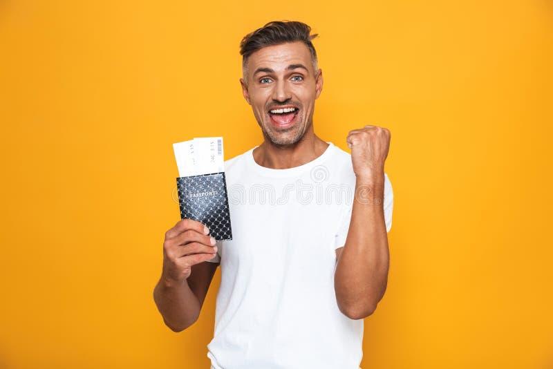 Wizerunek atrakcyjny mężczyzna 30s w białym koszulki mieniu paszportowym i podróż biletach obrazy royalty free