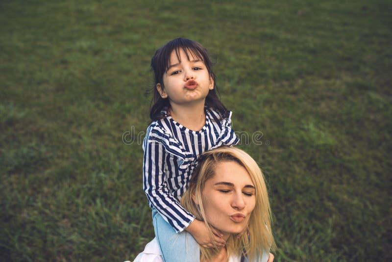 Wizerunek bawić się buziaka z jej śliczną małą dziewczynką na zielonej trawie plenerowej i dmucha piękna kobieta Kochająca ładna  zdjęcie stock