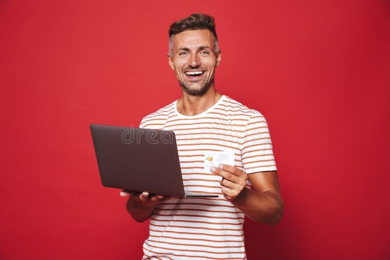 Wizerunek brunetka mężczyzna ono uśmiecha się w pasiastej koszulce podczas gdy trzymający c zdjęcia royalty free