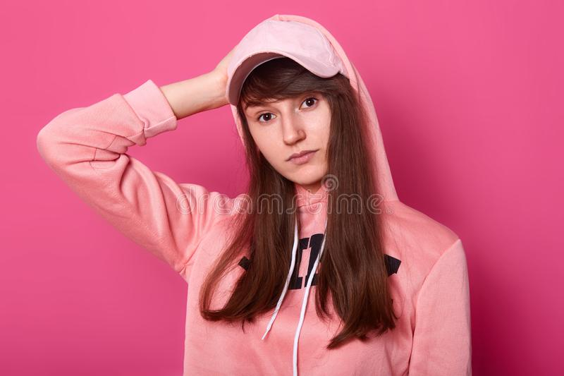 Wizerunek brunetki dziewczyny spojrzenia przy kamer? z powa?nego i thoufgtfull wyrazem twarzy, b?d?cy ubranym przypadkowy r??owy  zdjęcie royalty free