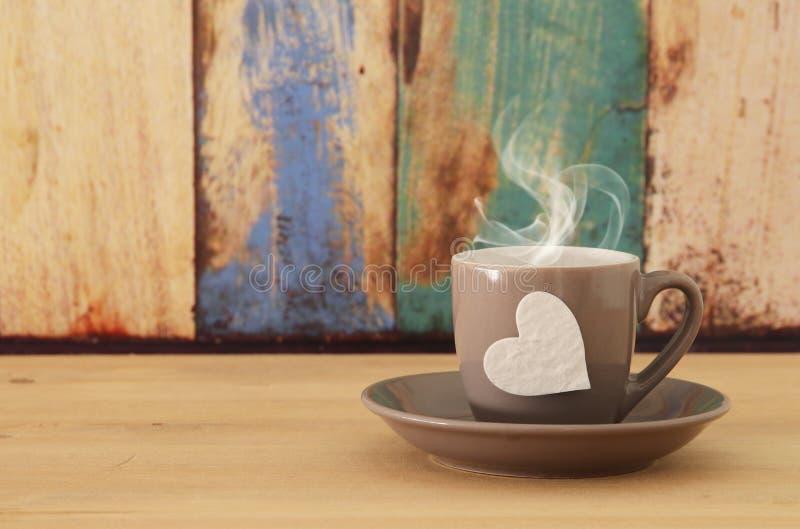 Wizerunek coffe filiżanka z sercem nad drewnianym stołem obraz royalty free