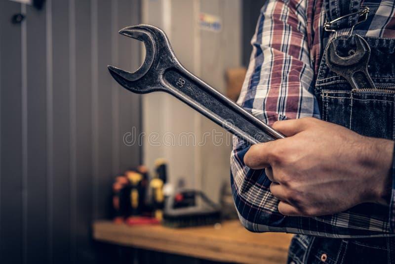 Wizerunek dokrętka klucz w mechanika ` s ręce zdjęcie royalty free