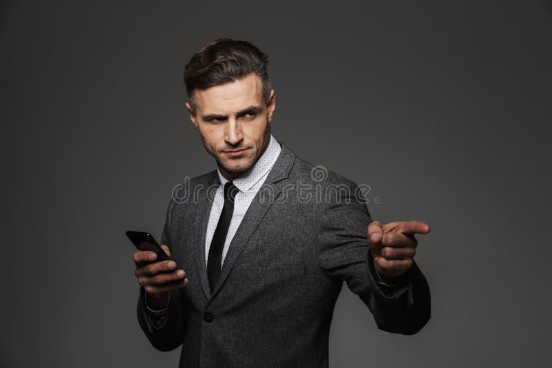 Wizerunek dorosły mężczyzna z surowym spojrzeniem w biznesowym kostiumowym mieniu zdjęcia stock