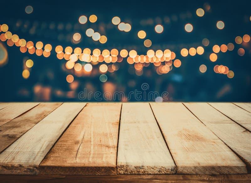 Wizerunek drewniany stół przed abstrakt zamazującą restauracją zaświeca tło fotografia royalty free