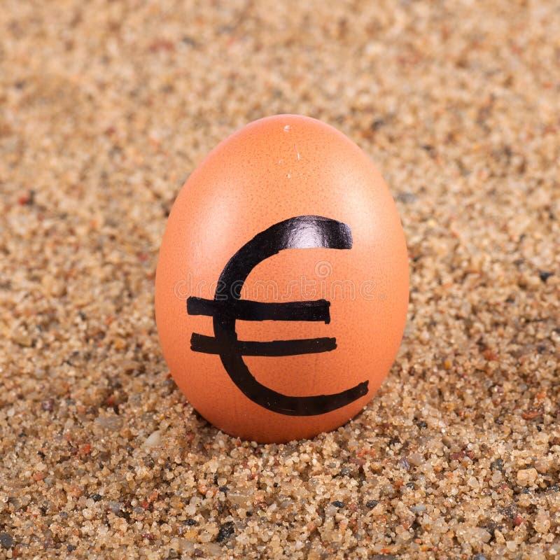 Wizerunek duży biały jajko z euro znakiem na piasku fotografia royalty free
