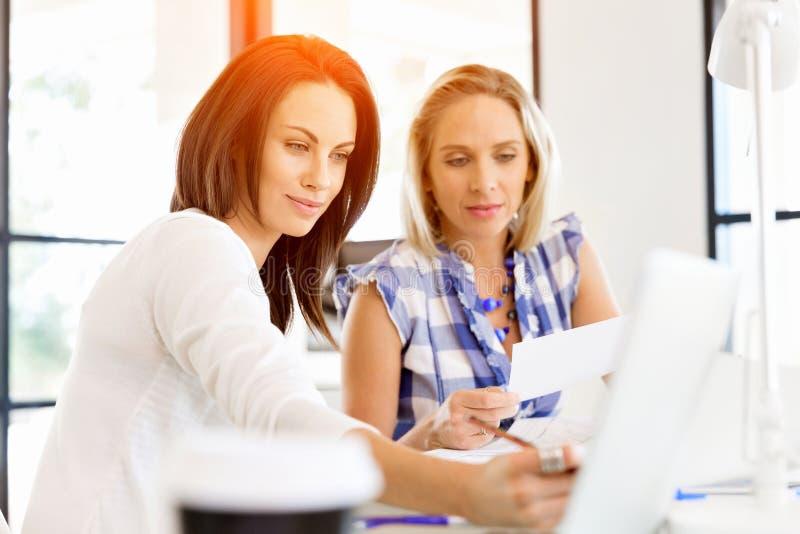 Wizerunek dwa młodej biznesowej kobiety w biurze obrazy stock