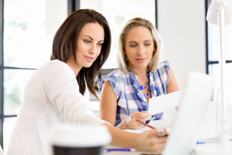 Wizerunek dwa młodej biznesowej kobiety w biurze zdjęcie stock