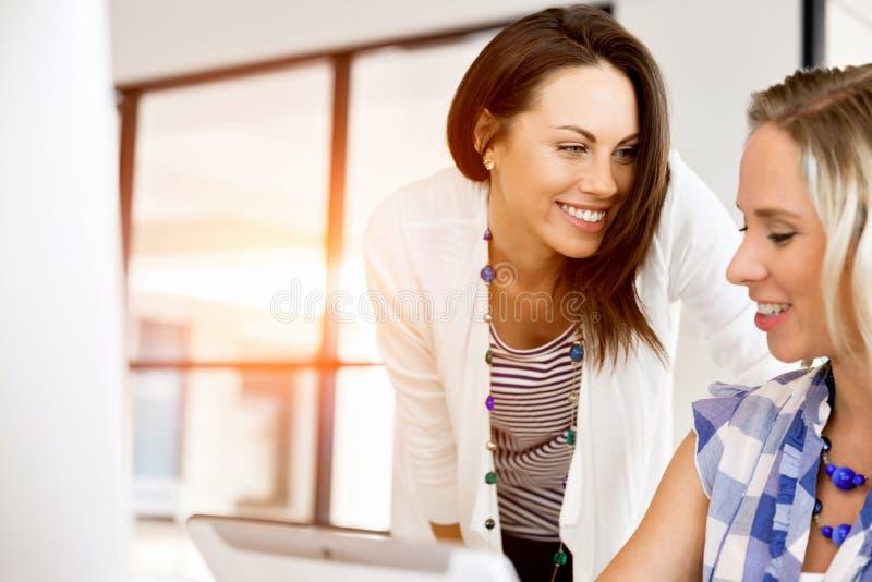 Wizerunek dwa młodej biznesowej kobiety w biurze zdjęcia stock