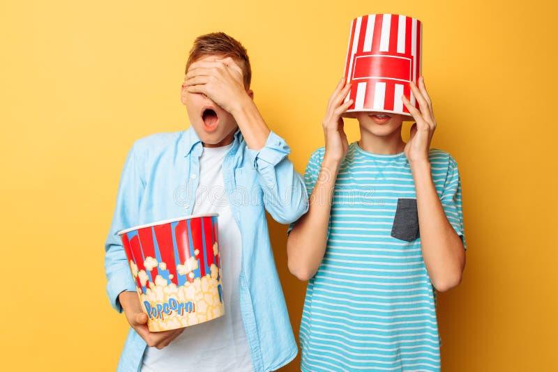Wizerunek dwa przestraszył nastolatków, faceci ogląda horror i chuje za wiadrem popkorn na żółtym tle fotografia royalty free