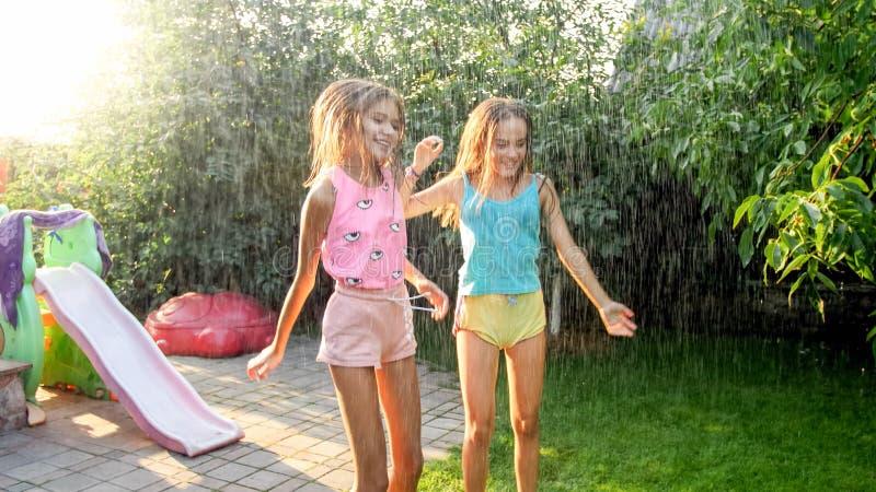 Wizerunek dwa szcz??liwej roze?mianej nastoletniej dziewczyny skacze i tanczy pod ciep?ym lato deszczem przy domowym podw?rko ogr obraz royalty free
