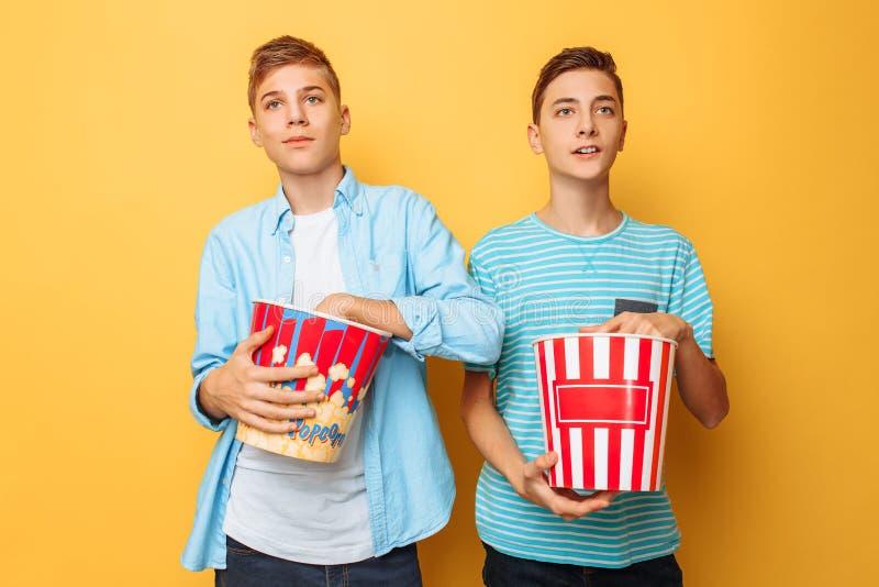 Wizerunek dwa z podnieceniem pięknego nastolatka, faceci ogląda ciekawego film i je popkorn na żółtym tle obraz royalty free