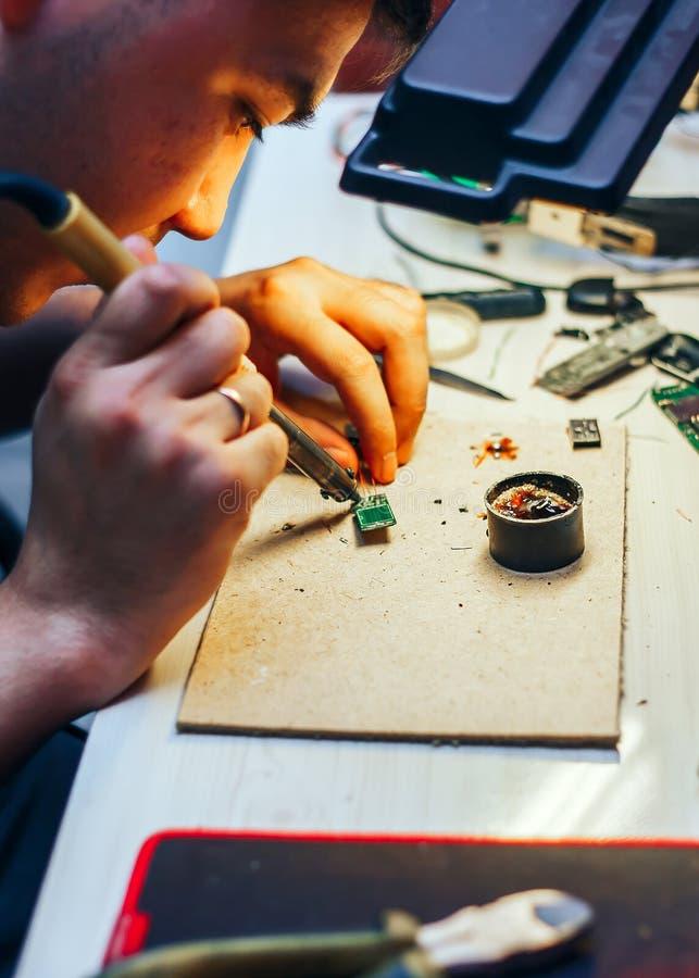 Wizerunek inżynier z lutowniczego żelaza naprawiania mechanizmem fotografia stock