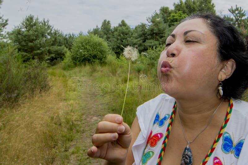 Wizerunek kobieta dmucha dandelion kwiatu w pięknym dniu fotografia royalty free