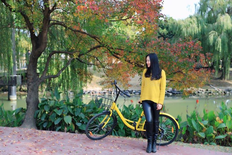 Wizerunek kobieta z bicyklem w parku fotografia stock