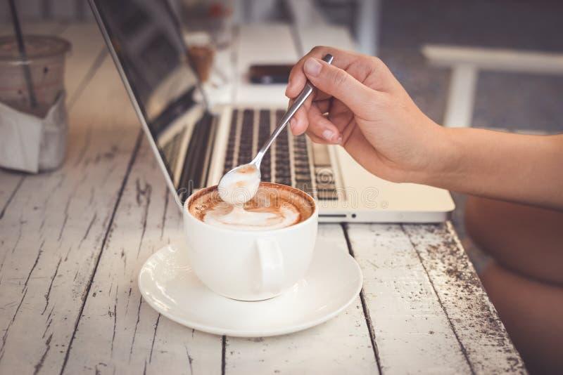 Wizerunek kobiety pije kawę i działanie z jej komputerowym laptopem przy sklepem z kawą zdjęcia royalty free