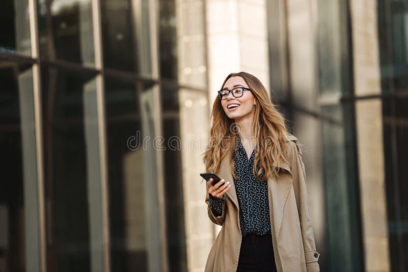 Wizerunek młoda kobieta używa telefon komórkowego podczas gdy chodzący przez miasto ulicy fotografia royalty free