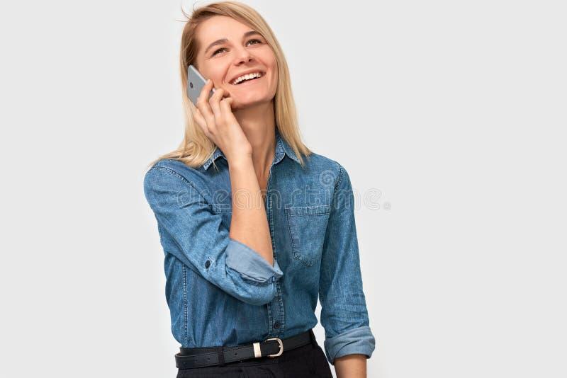 Wizerunek młoda piękna blondynki kobieta w drelichowy koszulowy ono uśmiecha się i opowiadać na mądrze telefonie jej przyjaciel,  zdjęcia stock