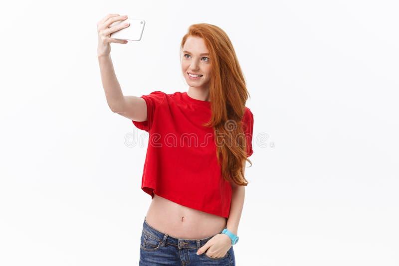 Wizerunek młoda szczęśliwa rudzielec kobieta odizolowywająca nad biel ściany tłem robi selfie przyglądającej kamerze obraz royalty free
