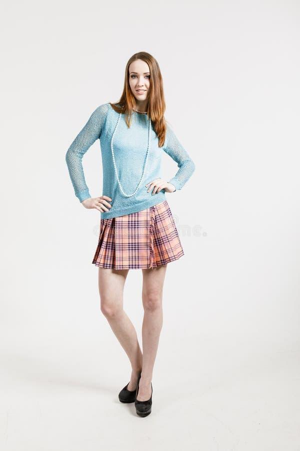 Wizerunek młoda kobieta jest ubranym krótką spódnicę i turkusowego pulower zdjęcia stock