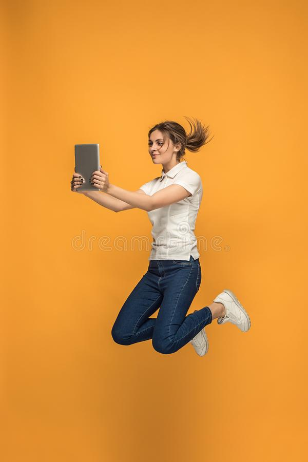 Wizerunek młoda kobieta nad pomarańczowym tłem używać laptopu lub pastylki gadżet podczas gdy skaczący fotografia royalty free